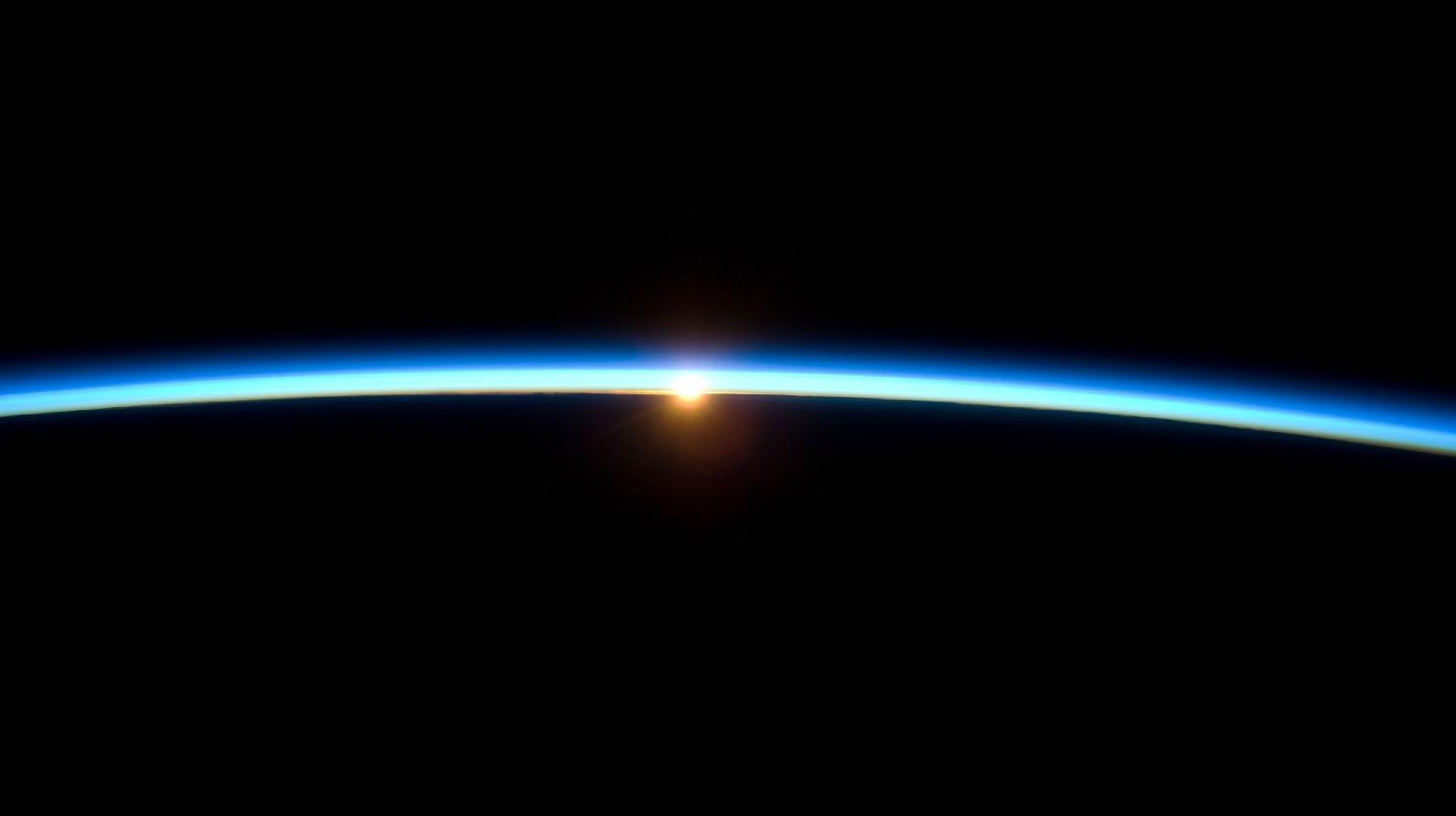 Linia fină a atmosferei terestre şi soarele la apus.