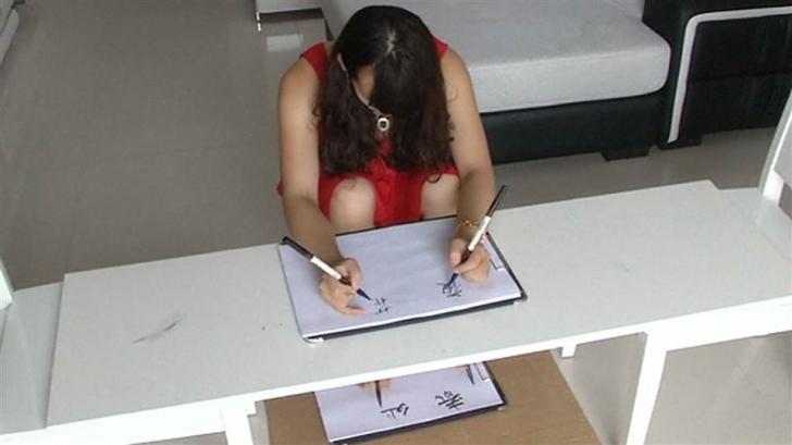 O tânără din China poate să scrie cu mâinile şi picioarele, în acelaşi timp