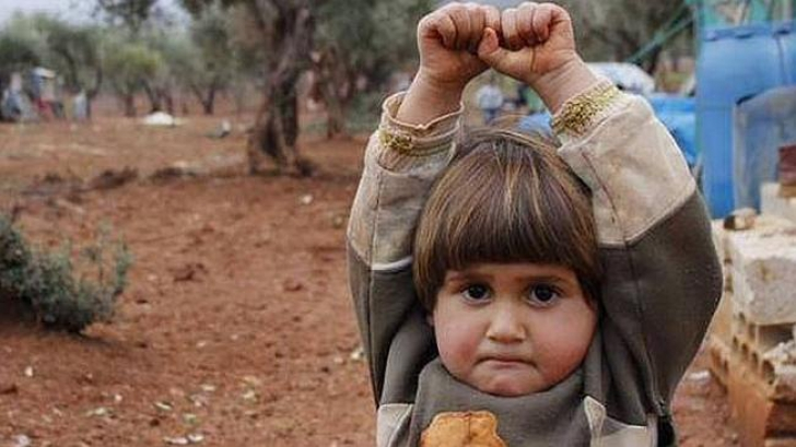 """Fetiţa care se """"predă"""" în faţa obiectivului foto. Povestea imaginii care face furori pe Internet"""