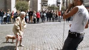 O bătrânică se opreşte în centrul unei pieţe şi face asta. Toată lumea este uimită