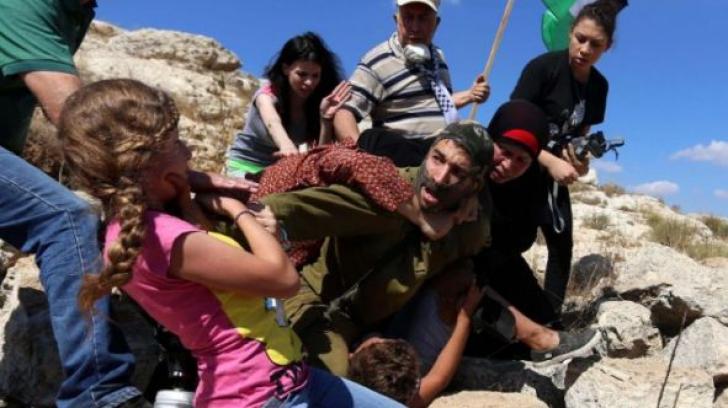 Imagini scandaloase! Un militar imobilizează, sub amenințarea armei, un copil cu mâna în ghips