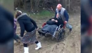 Imagini revoltătoare. O bătrână în scaun cu rotile, transportată de săteni până la ambulanţă