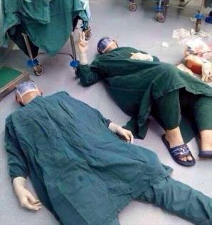 Poza cu aceşti doi chirurgi întinşi pe podea a cucerit internetul! Explicaţia fabuloasă