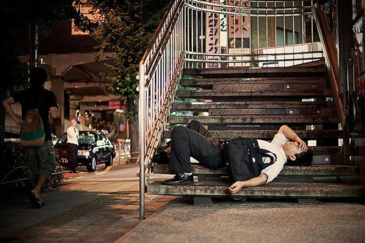 Poze incredibile cu angajaţii epuizaţi din Tokyo care adorm pe străzi