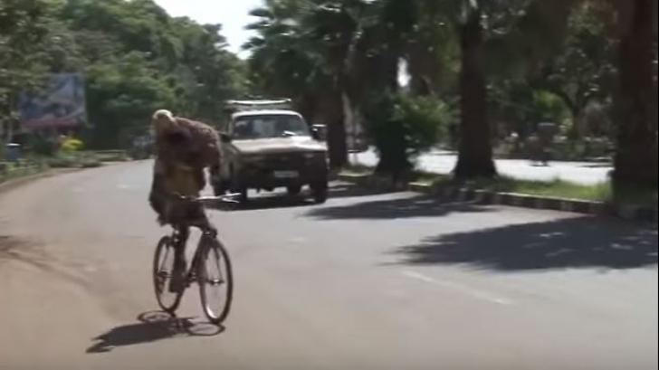 Șoferii, înmărmuriți. Ce duce în spate acest biciclist, în plină stradă