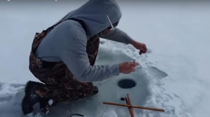 Au tot tras de firul lăsat în apa înghețată până când...ȘOC. Ce creatură au scos prin copcă
