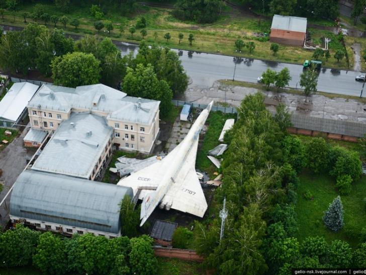"""Imaginea bizară surprinsă din dronă. Avionul supersonic """"ascuns"""" în spatele blocului"""