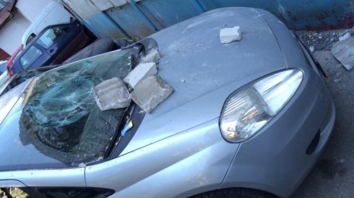 O cărămidă de pe un horn s-a desprins și a căzut pe o mașină