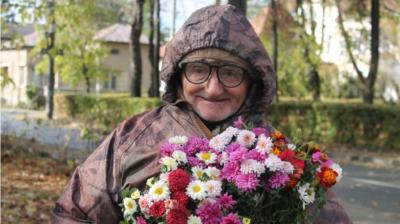 Acest bărbat vinde flori în Parcul Copou, în Iaşi. Pe pancartă a scris mesajul care aduce zâmbete