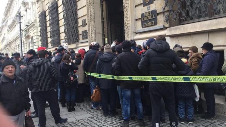 Românii au luat cu asalt sediul BNR. Stau la coadă pentru bani