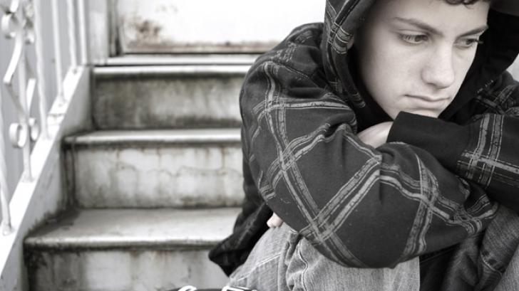 Copil care stă retras într-un colț