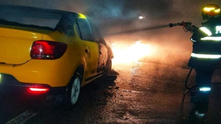 Taxi în flăcări pe un drum din apropiere de Valea Plopilor! De ce a luat foc mașina