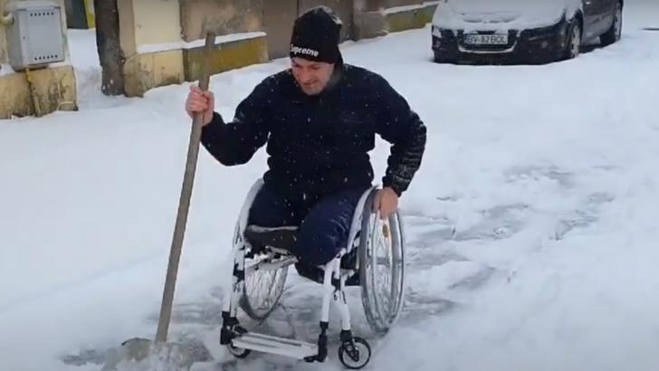Bărbat din jud. Brasov curăță zăpada, deși este țintuit in scaun cu rotile. (foto: captura video Robert Elekes)