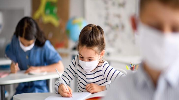 Elevi cu mască în sala de clasă