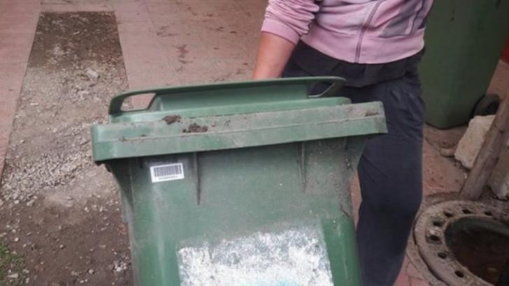 O femeie a fost surprinsă în timp ce transporta cadavrul unui bărbat într-un tomberon