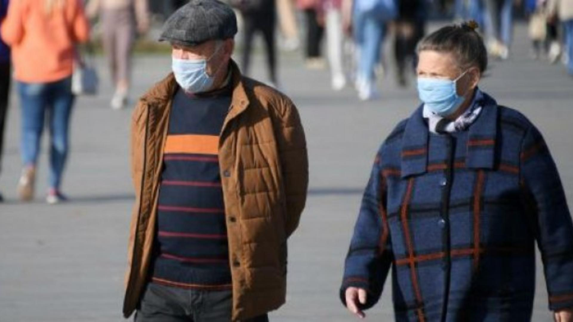 Oameni cu mască pe stradă
