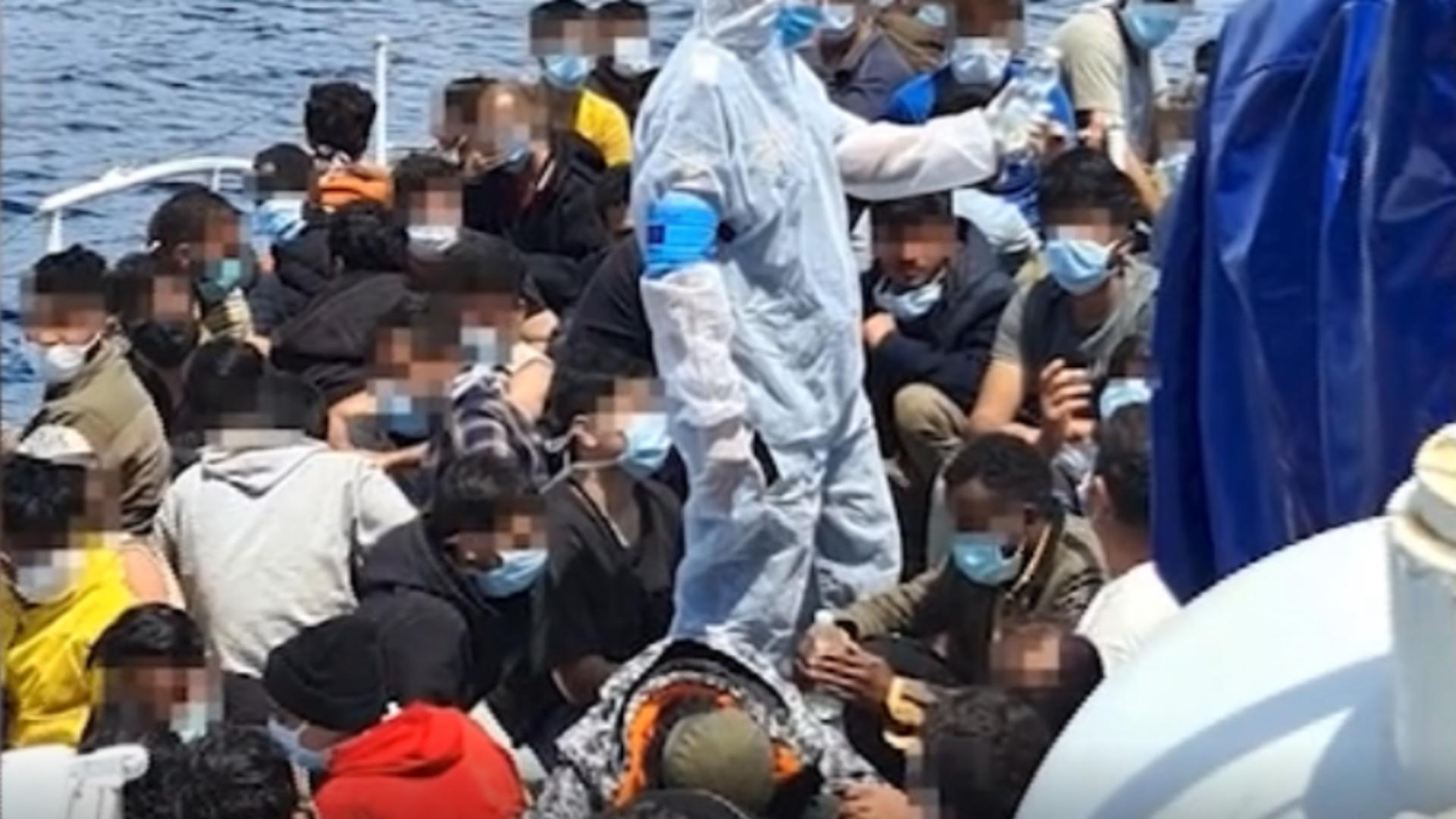 Sute de migranți de pe un vas ce risca să se scufunde, aduși la mal