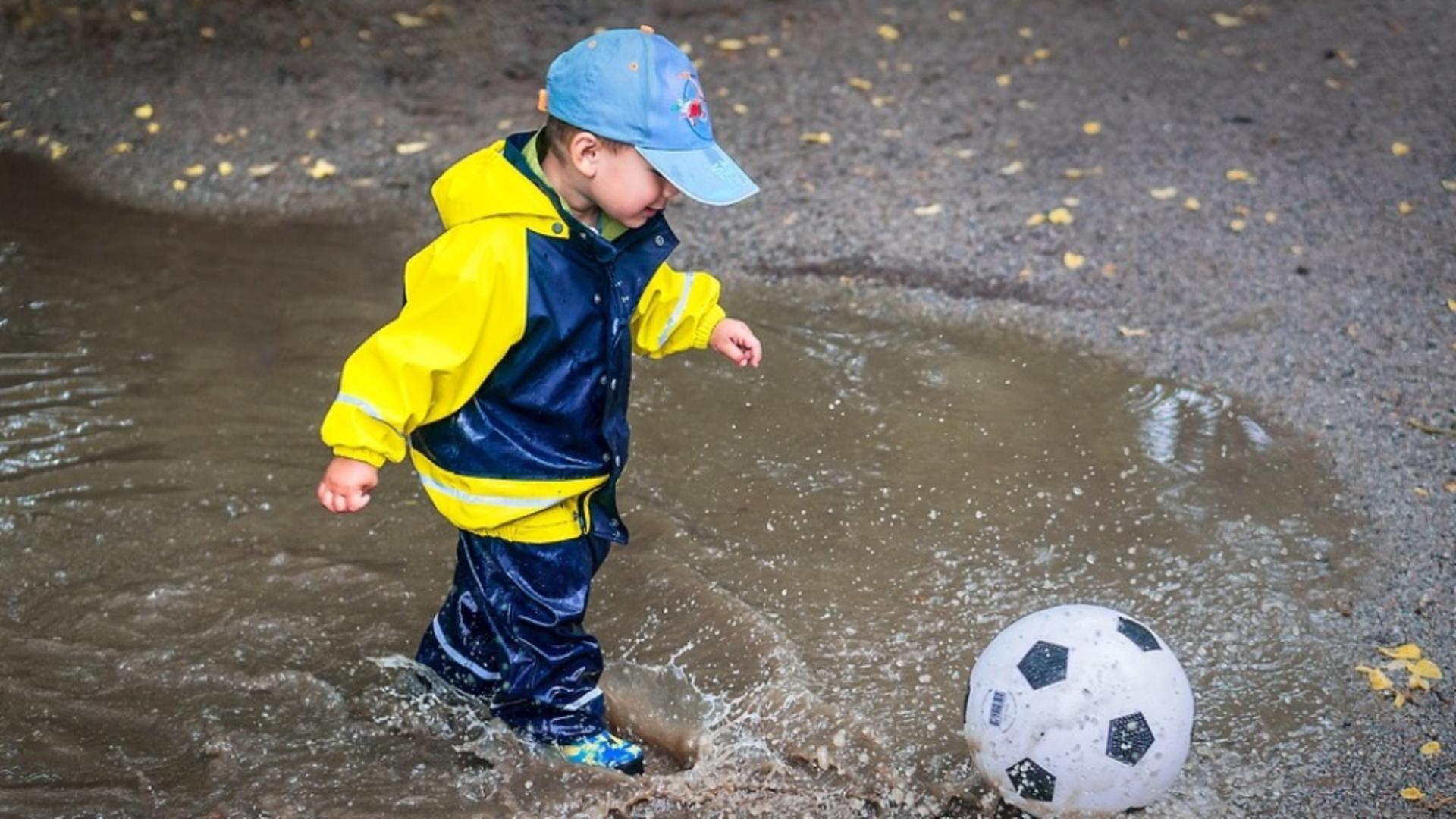 Copil care se joacă în ploaie