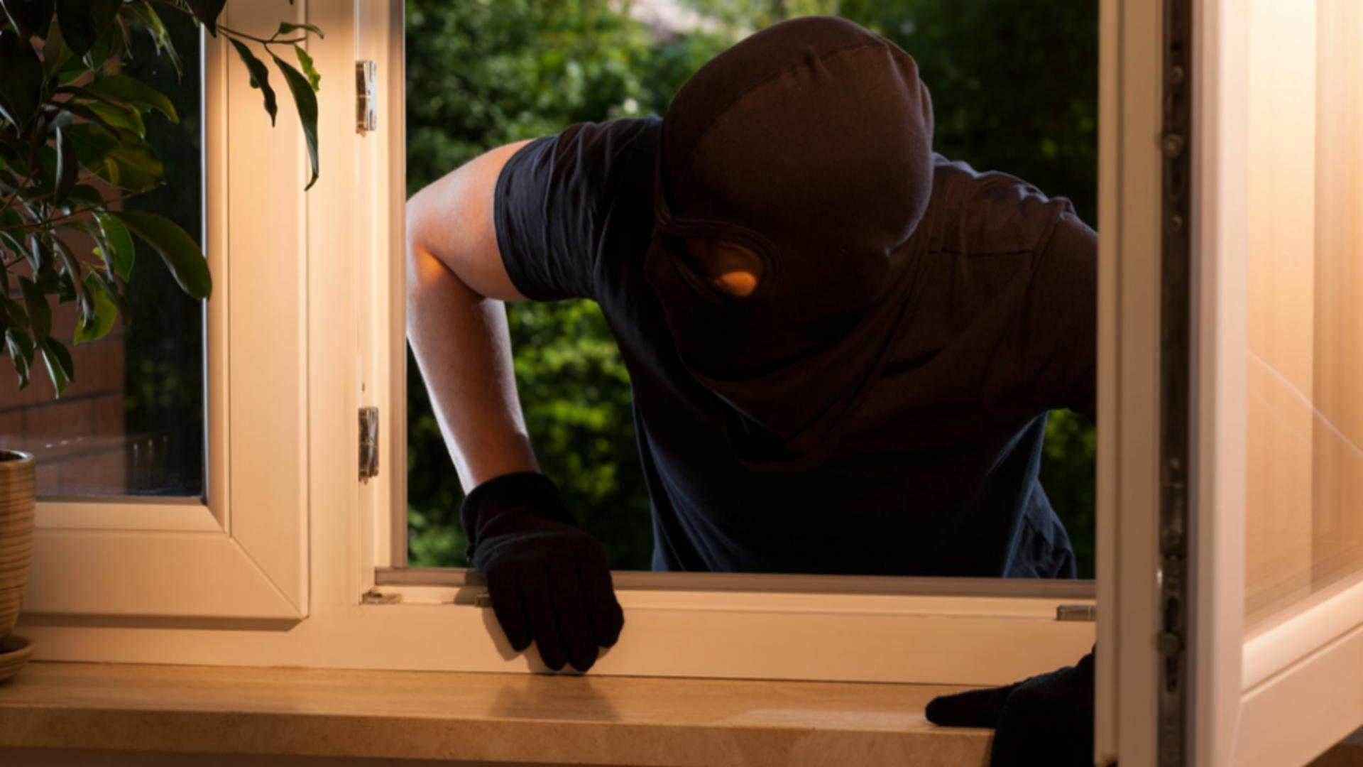 Hoț care escaladează o fereastră