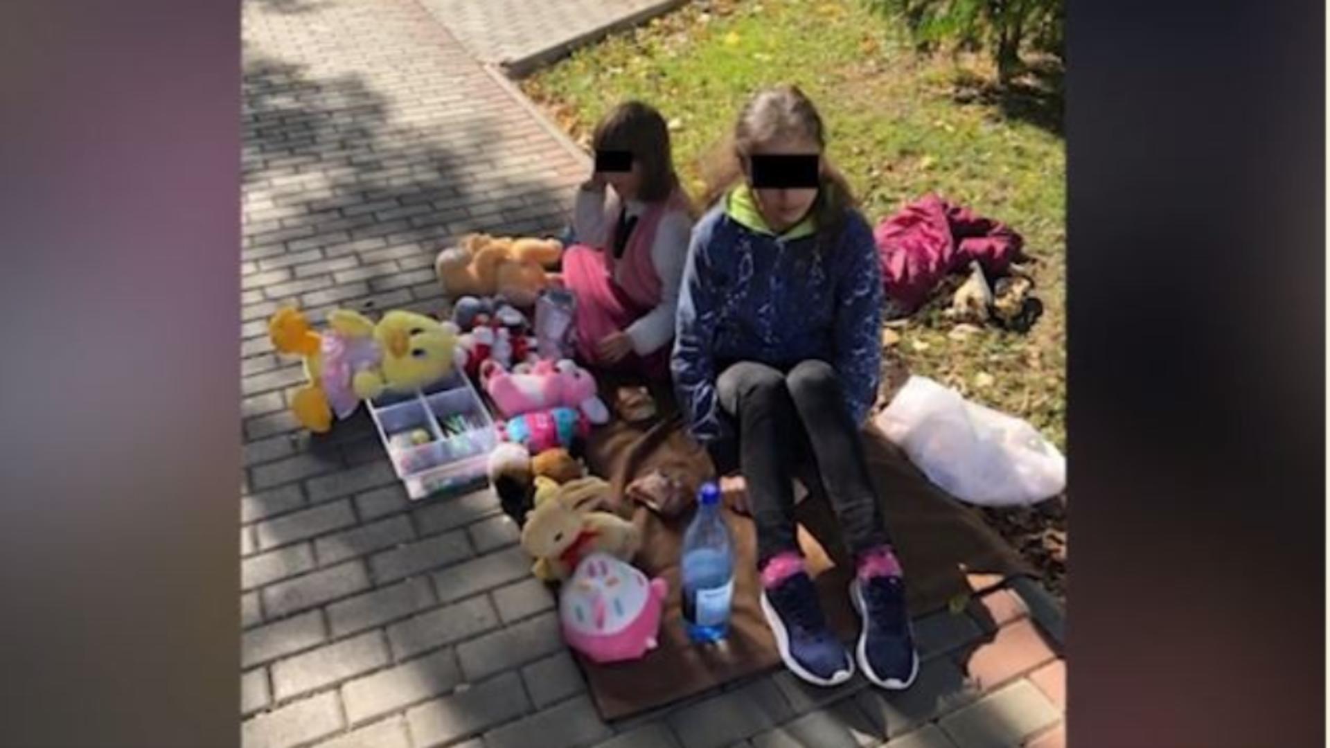 Două fetițe își vând jucăriile pe o pătură, în fața unui liceu