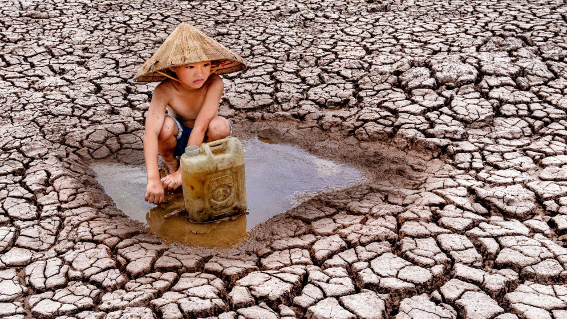 Un băiețel fotografiat adunând ultimele picături de apă. Sursa foto: Profi Media