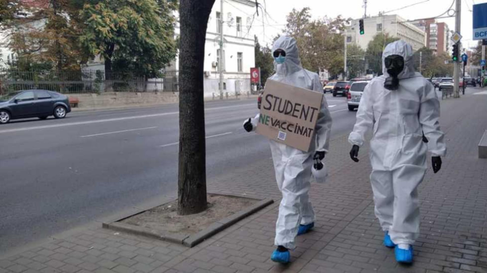 Imaginea MOMENTULUI! Doi studenţi din Iași protestează împotriva vaccinării anti-Covid-19 îmbrăcați în combinezoane